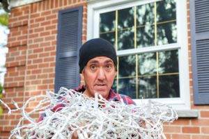 Image of homeowner struggling with outdoor Christmas Lights