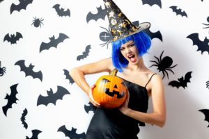 Image of attractive funny young woman in Halloween Costume at party holding a pumpkin