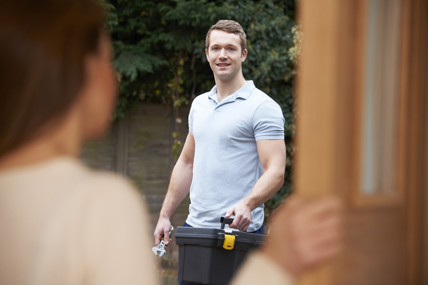 Help for Hire, smiling handyman with tool bag greeting senior at front door
