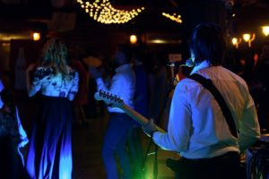 Entertainers at a wedding ball, Image shows a performer in a band playing a guitar