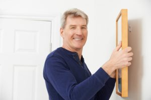 local odd job man hanging a picture